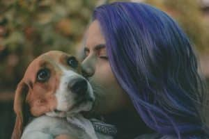 woman with purple hair kissing side of dogs face