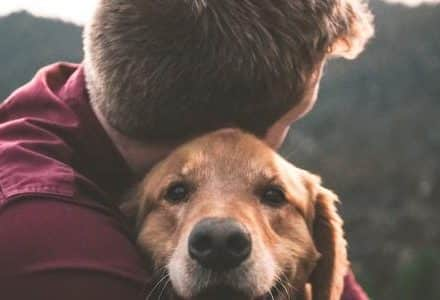 man cuddling dog