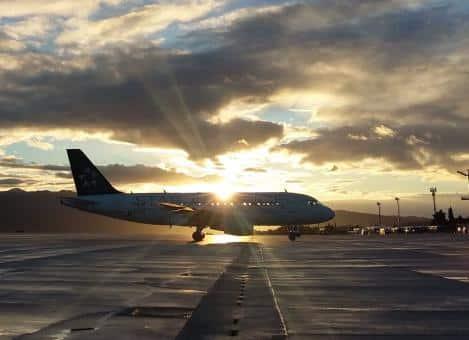 a plane an an airport at sunset