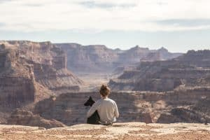 girl and dog sitting on top of a canyon